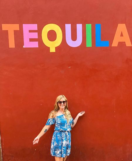 Young woman standing against wall with tequila text