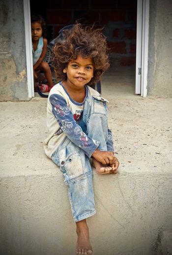Portrait of smiling girl standing outside house