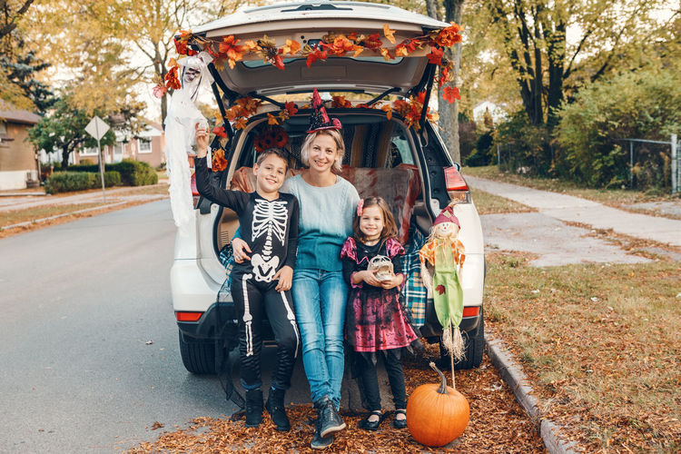 Trick or trunk. family celebrating halloween in trunk of car. mother with kids