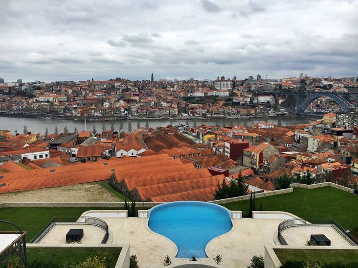 Dom luis i bridge over douro river in town against cloudy sky