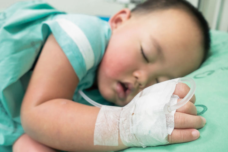 Close-up of boy sleeping on bed in hospital