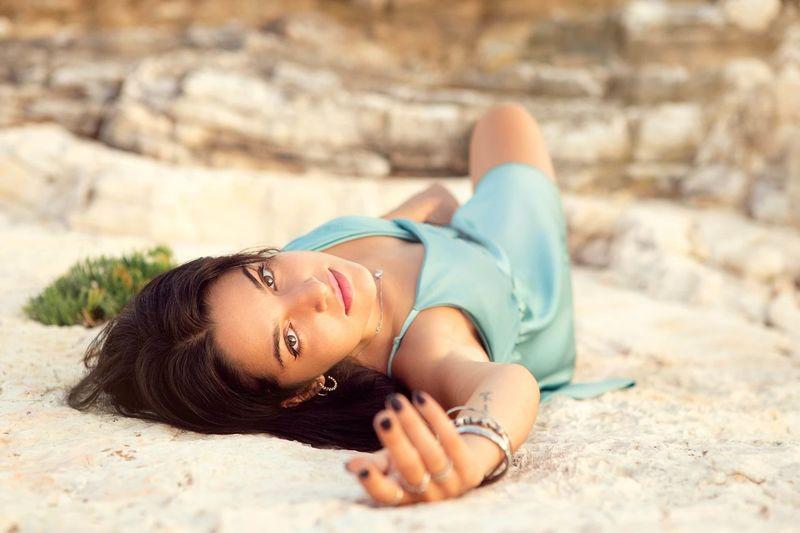 Portrait of woman lying on sand