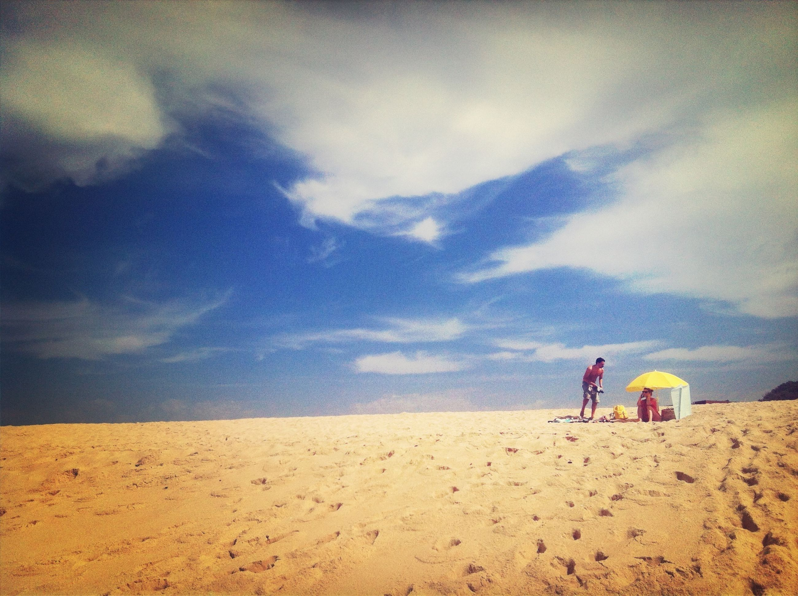 sand, beach, leisure activity, sky, lifestyles, men, full length, cloud - sky, childhood, shore, tranquility, vacations, tranquil scene, scenics, rear view, casual clothing, nature