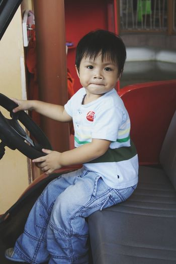 Portrait of cute boy sitting in vehicle