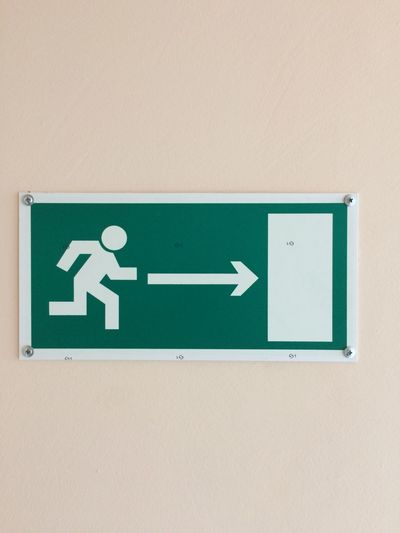 Close-up of exit sign on wall