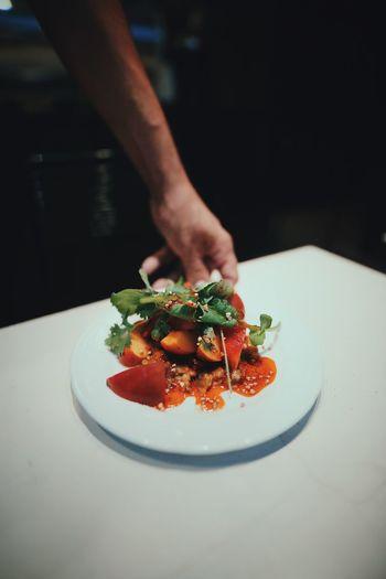 Cropped hand preparing food in restaurant
