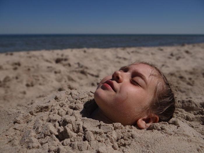 Close-up of girl sleeping on beach