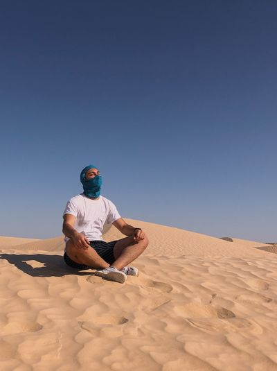 Low angle view of man sitting on sand dune in desert against sky