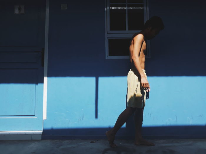 Rear view of shirtless man standing in blue house