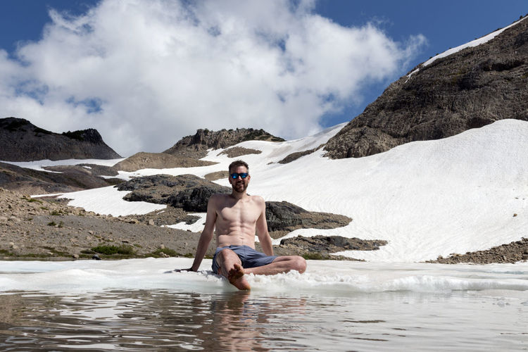 Glacier fed lake with man enjoying a break from hiking wearing shorts enjoying the warm sun while sitting on sitting on ice. Expedition Sitting Adult Alpine Lake Break Caucasian Cloud - Sky Cold Fitness Floating On Water Hiker Iceberg Leisure Activity Mountain Mountain Range Muscle Nature Outdoors Relax Resting Shirtless Skin Care Sky Sun Water