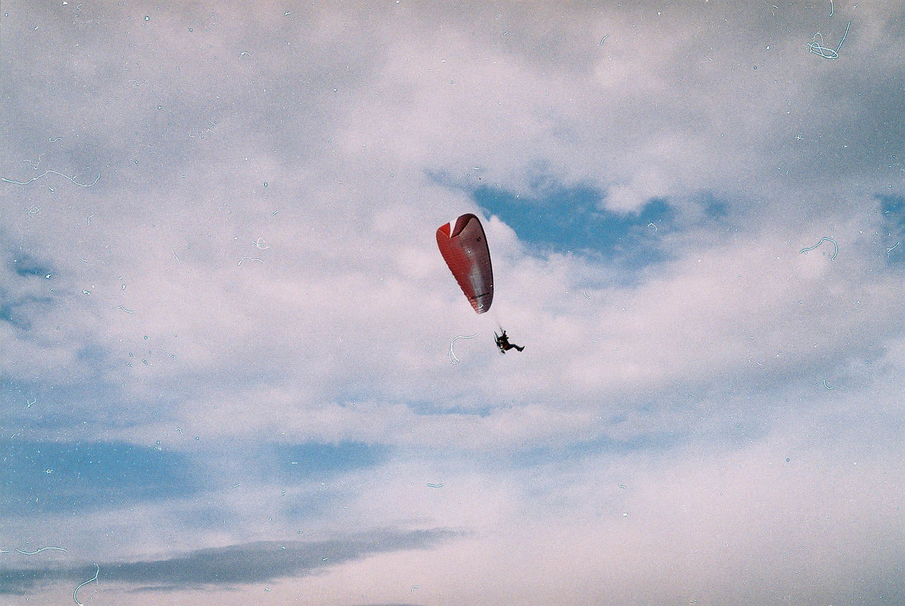 LOW ANGLE VIEW OF PERSON FLYING KITE AGAINST SKY