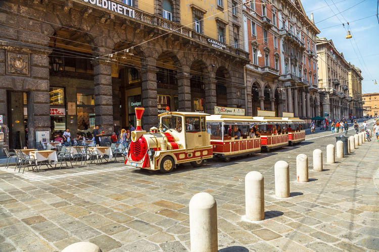 Bologna, Italy - May 28, 2016: Palazzo Re Enzo, historical landmark palace and heart of economic and social activities of the city with many people and the main square called Piazza Maggiore. People walking in via Rizzoli, restricted traffic zone, closed to traffic during the day on Saturday. The Two Towers, icons of Bologna, on background. Tourist train at side of Palazzo dei Banchi in Piazza Maggiore. San Luca Espress is the tourist line which connects the historic center with the Basilica of San Luca. Bologna Bologna, Italy Cathedral Church City Piazza Maggiore San Luca Tourist Architectural Column Architecture Asinelli Asinelli Tower  Building Building Exterior Built Structure City Day Group Of People History Incidental People Italian Italy Men Mode Of Transportation Nature Old Outdoors People Real People San Petronio Street Streetphotography Sunlight The Past Tourism Town Train Transportation Travel