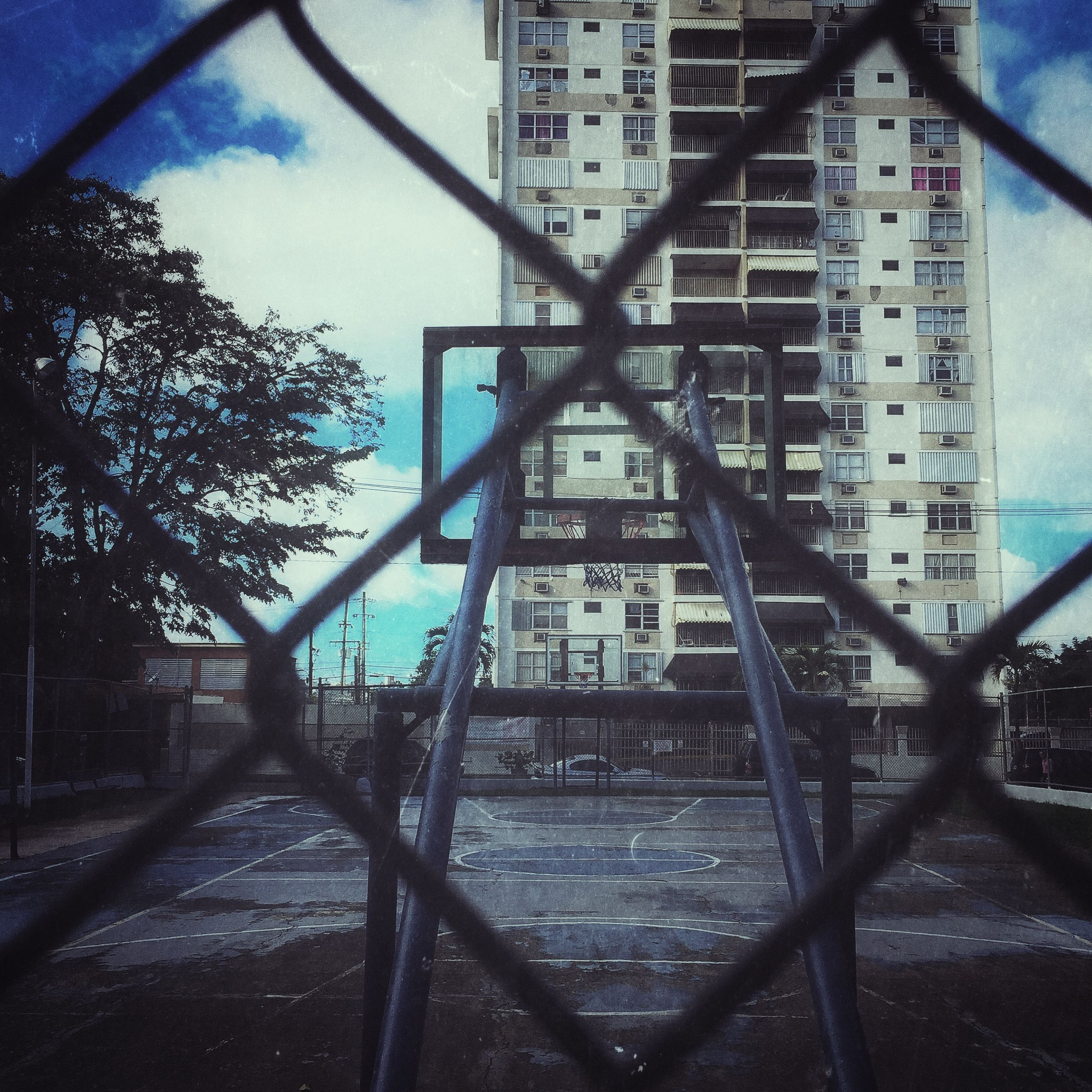 architecture, built structure, building exterior, city, building, residential building, residential structure, railing, sky, day, the way forward, outdoors, no people, window, street, sunlight, chainlink fence, shadow, house, reflection