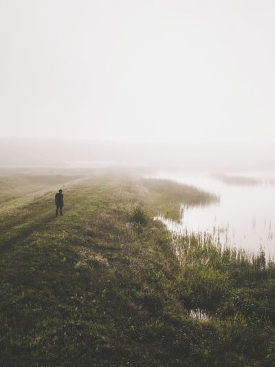 Grass Nature Field Water Landscape Day Beauty In Nature Outdoors Tranquility Scenics Fog One Person Lifestyles Lake Full Length Real People Sky People