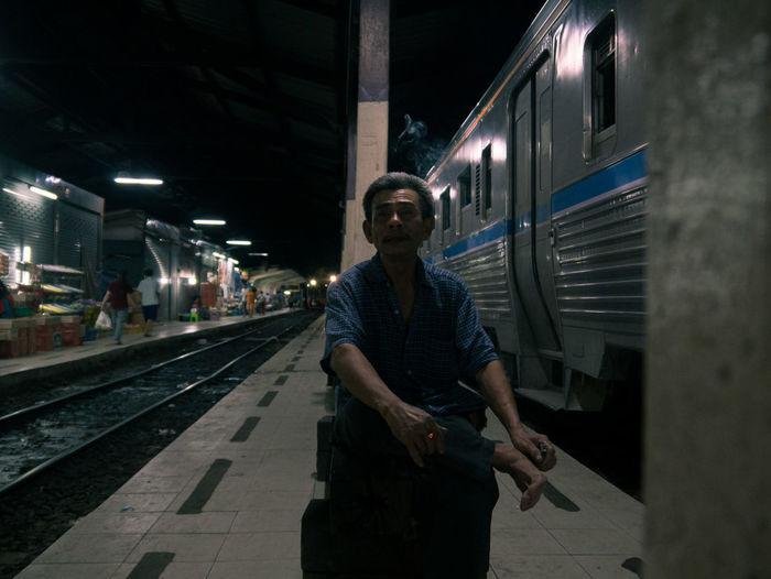 Portrait of man sitting at railroad station platform