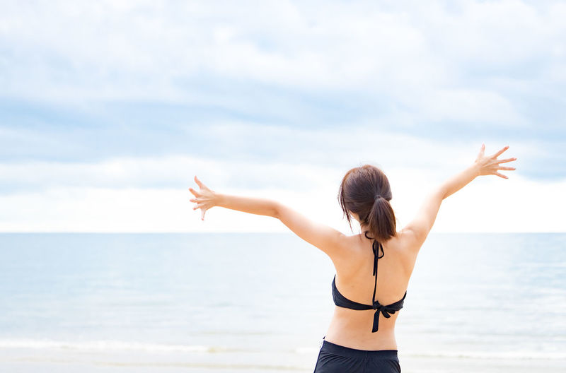 Rear view of young woman standing in sea against sky