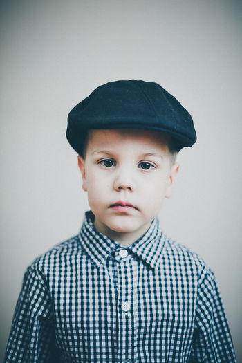 Portrait of boy in beret cap over gray background