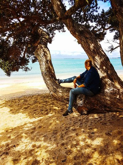 Man sitting on tree trunk by sea against sky