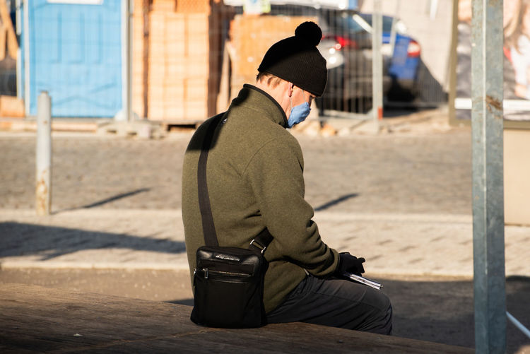 Side view of man wearing hat sitting in city