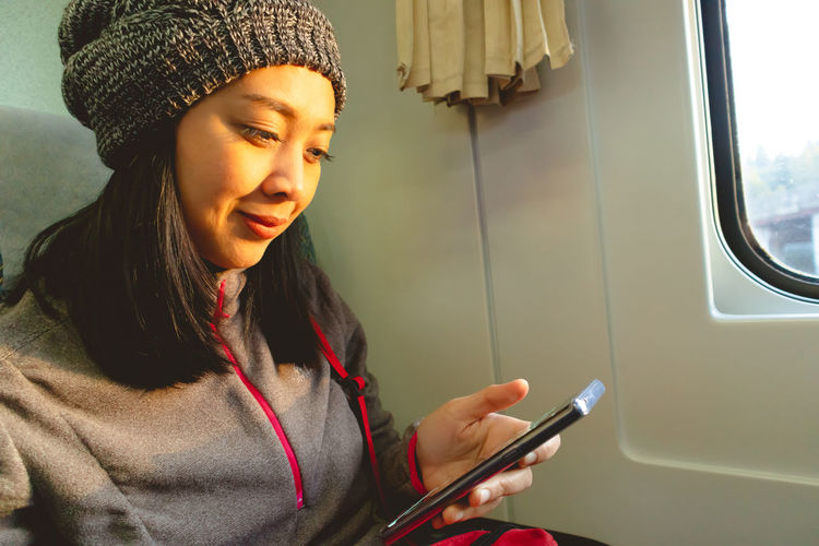 Close-up of woman using mobile phone while sitting in train