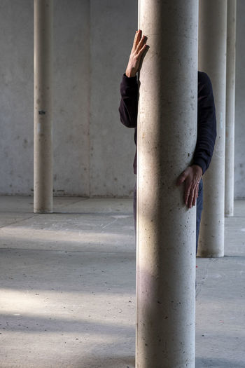 Midsection of woman with umbrella standing on concrete wall