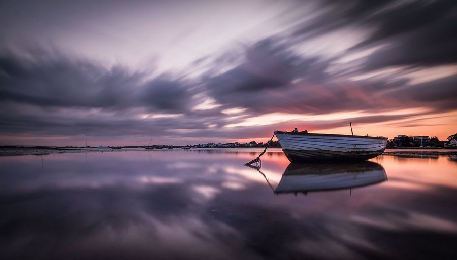 Rowboat Moored In Sea Against Sky During Sunset