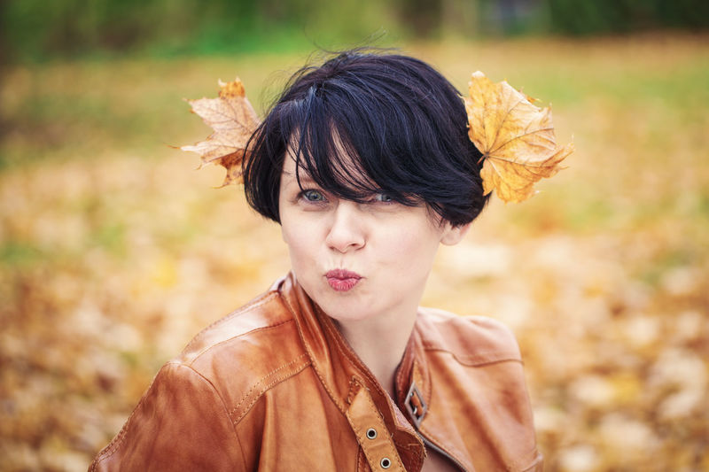 Portrait of smiling woman with autumn leaves on head