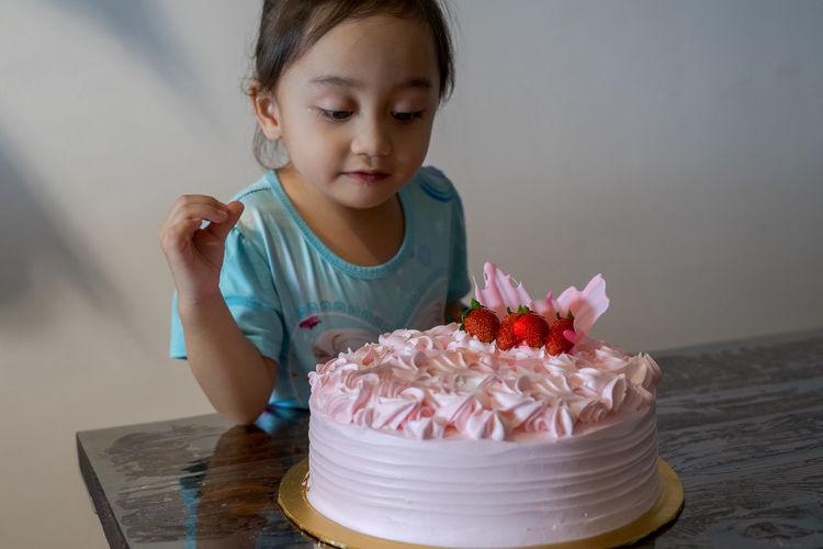 Cute girl holding ice cream on table