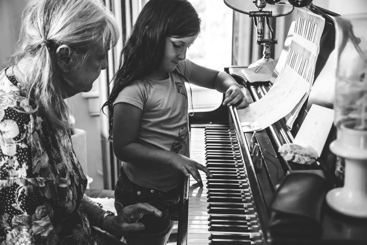 Grandmother Teaching Piano To Granddaughter At Home