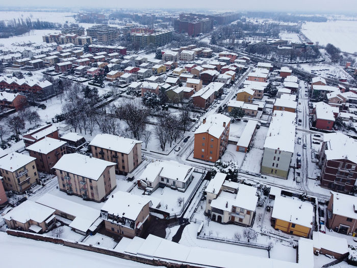 High angle view of snow covered houses in city