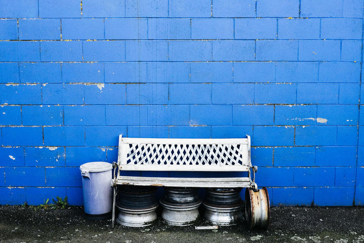 Empty Bench Against Blue Wall