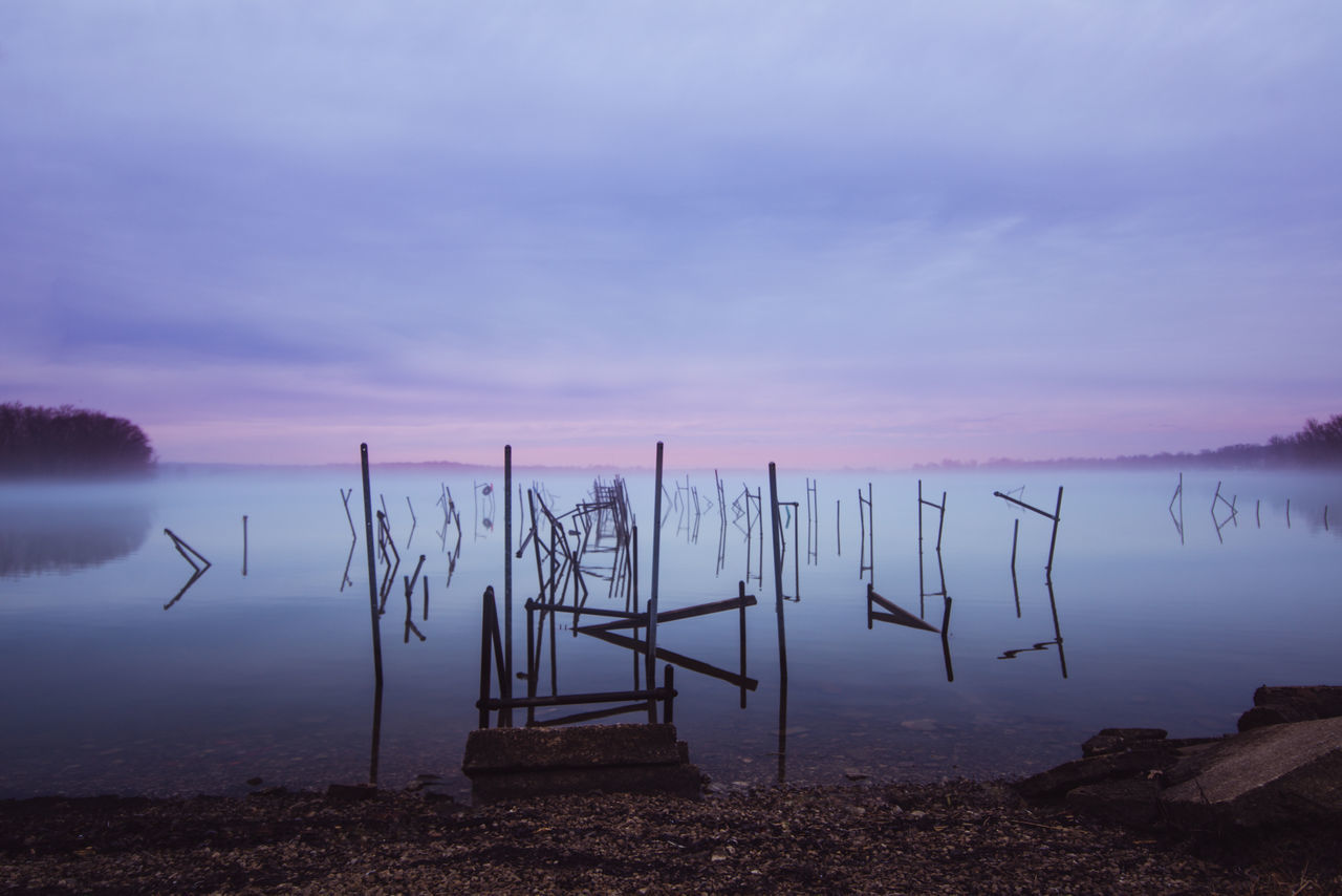 lake, water, tranquil scene, tranquility, nature, beauty in nature, scenics, reflection, no people, sunset, outdoors, sky, wooden post, day