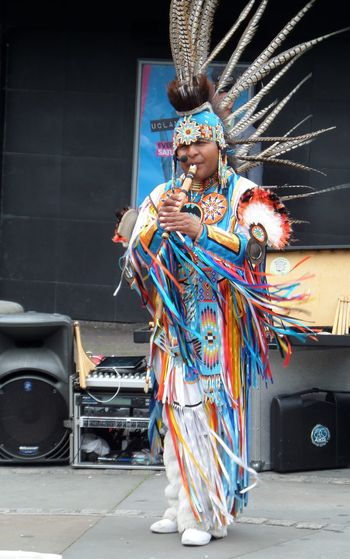 Colourful Costume. Ethnic. Exotic. Bloom Feathers. Front View Full Length Headdress. Looking At Camera Musician. Musician.pipes. Native. Outdoors Person Single Figure Playing Pipes Standing Street Musician.