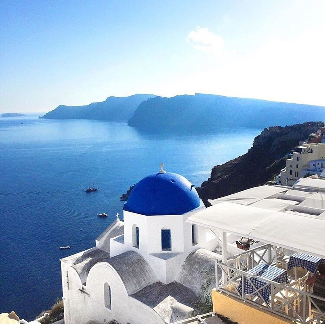 religion, architecture, sky, white color, built structure, whitewashed, spirituality, sea, water, day, blue, dome, place of worship, outdoors, building exterior, high angle view, nature, no people, roof, mountain, sunlight, beauty in nature, horizon over water, cross, travel destinations, scenics