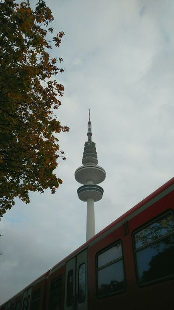 Heinrich-Hertz-Turm behind Train. · Hamburg Germany 040 Hh Heinrich Hertz Turm Radio Tower TowerLandmark Sternschanze Architecture Built Structure Behind A Train Framed By Trees Overcast Cloudy Gray Sky