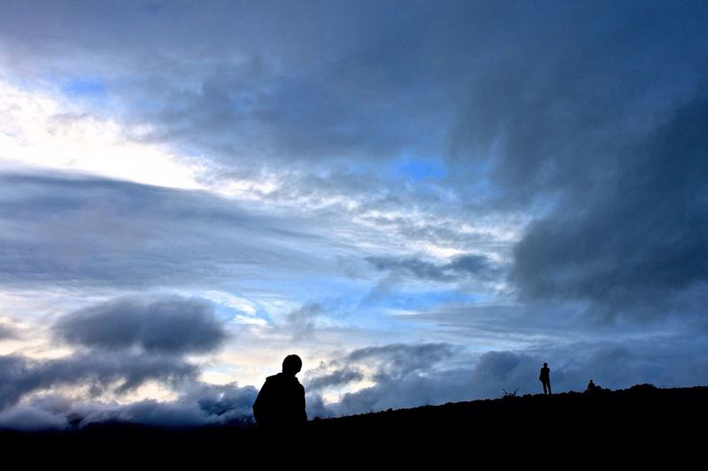Silhouettes Of Young Men Looking At View In Mountains