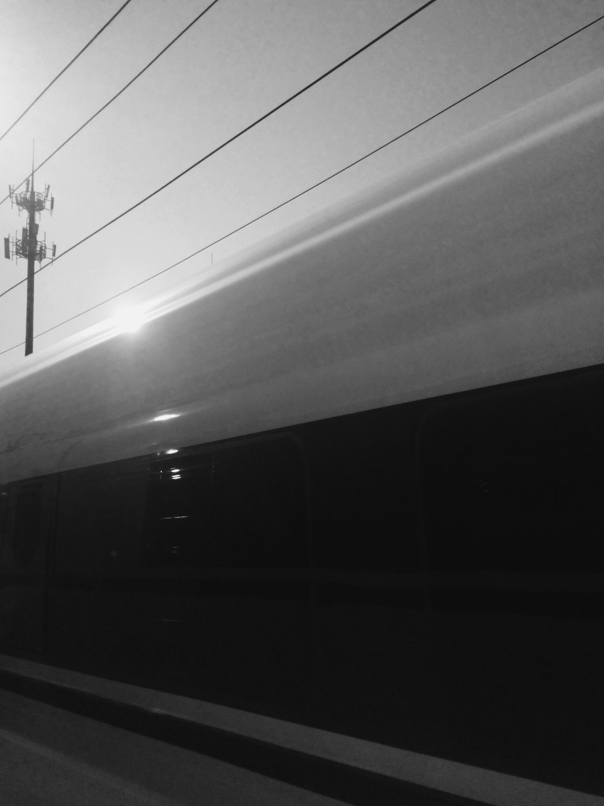 transportation, mode of transport, public transportation, rail transportation, railroad station platform, railroad track, connection, road, railroad station, train - vehicle, sky, land vehicle, built structure, travel, on the move, power line, car, architecture, illuminated, indoors
