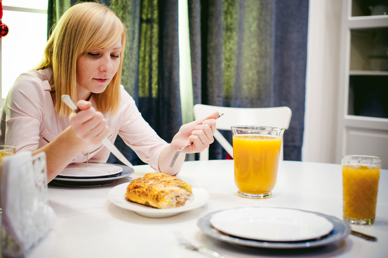 Young Woman Having Food And Drink While Sitting At Home