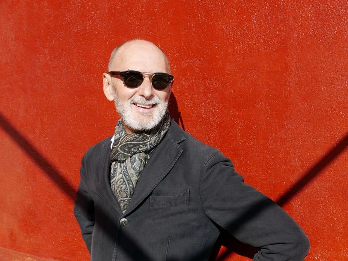 Smiling Senior Man Wearing Sunglasses While Standing Against Red Wall