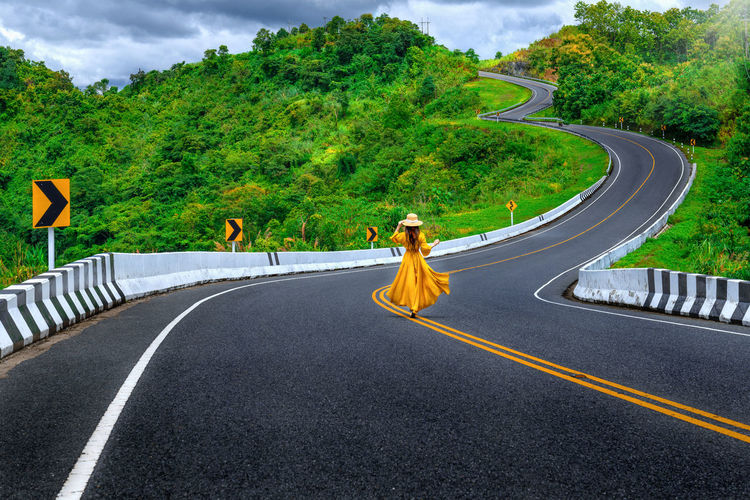 Woman in yellow dress walking on road amidst trees against sky