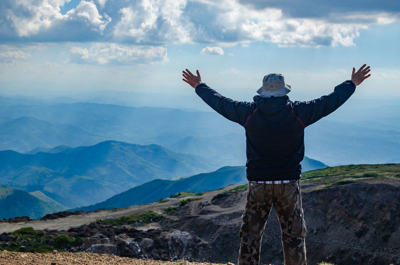 Hiker with spread arms in a joyful pose, on a mountain top watching a landscape