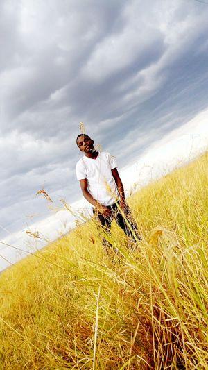 Tilt image of young man standing on grassy landscape