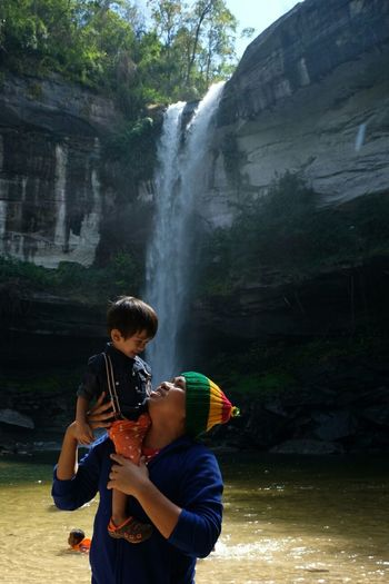 Man Carrying Son On Shoulder While Standing Against Waterfall