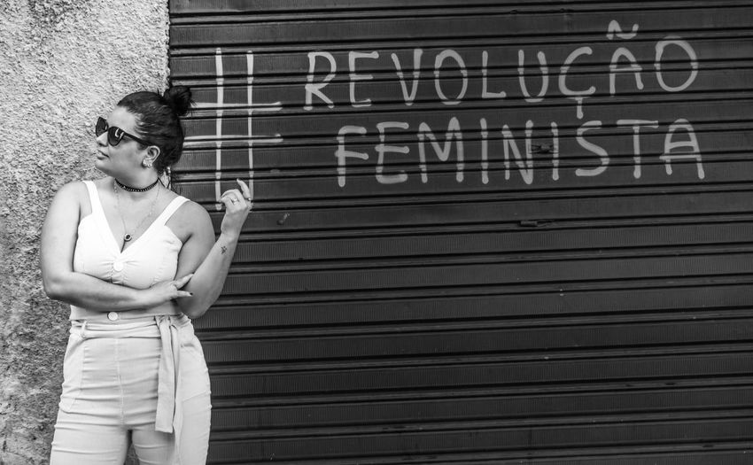 Woman standing against shutter with text