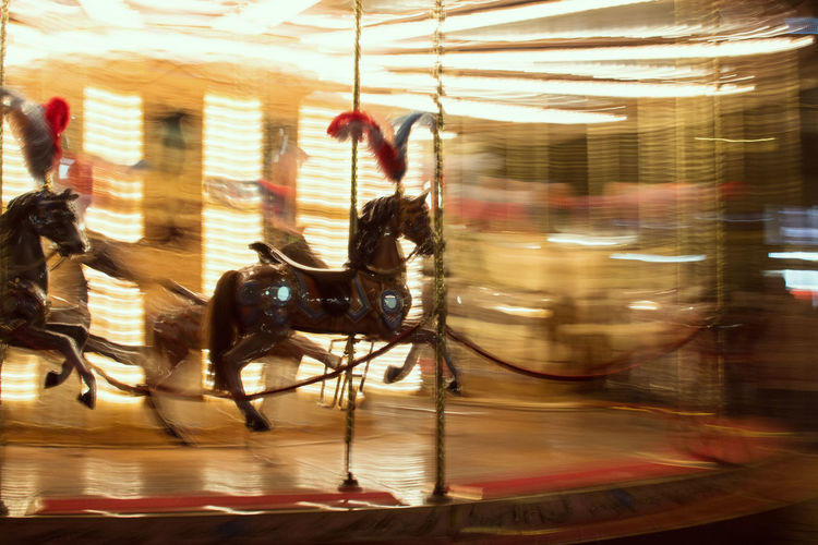 Blurred motion of people riding horses in amusement park at night