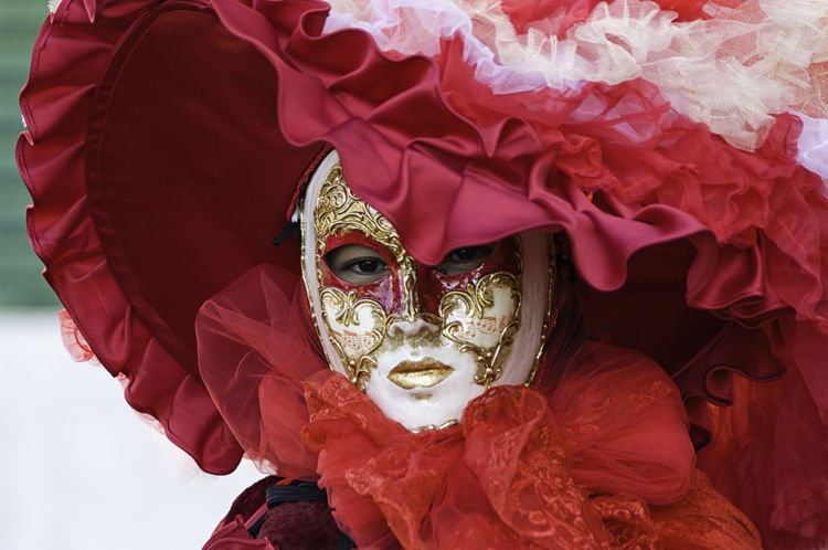 Portrait of a beautiful woman wearing a red dress and white mask during the Venetian carnival party in San Marco square Carnival Lady Masque Red Square Tradition Venetian Woman Carneval Close-up Concealed Costume Disguise Dressing Festival Hide Italy Mask Masquerade Mistery Portrait San Marco Traditional Unrecognizable Venice