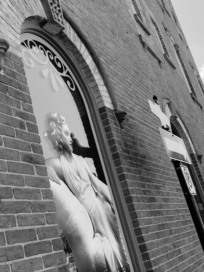 Street / Outdoor Photography series: Are you Marilyn Monroe or someone looks like her Advertising Propaganda Downtown District Whitby Ontario EyeEm Selects Architecture Built Structure Low Angle View Building Exterior Day Building No People Outdoors Sunlight Wall Sky Brick Wall The Past Travel Destinations History Arch City