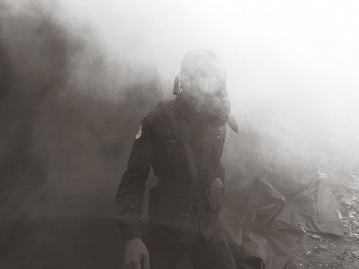 Person wearing gas mask standing amid smoke