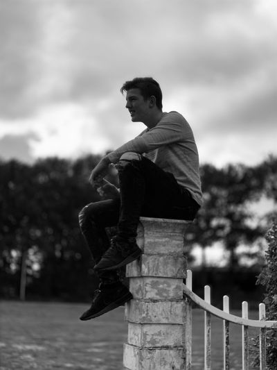 Side view of man sitting against sky