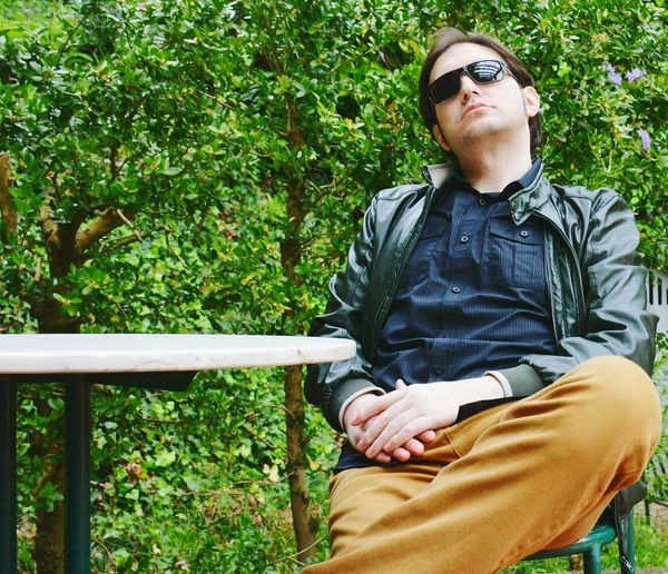 Mature Man Sitting On Chair Against Trees In Forest